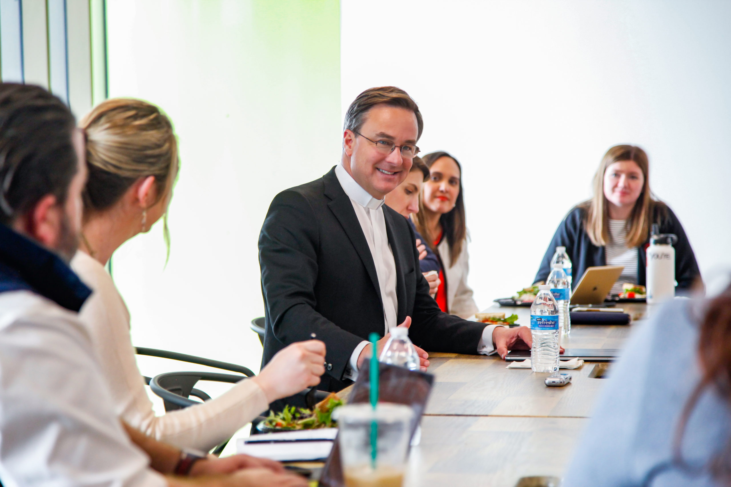 Creighton president Daniel Hendrickson sits at a conference room table speaking to members of the GPEC staff.