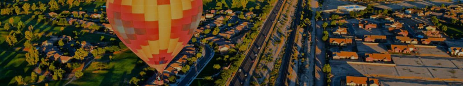 Aztec-style red and yellow hot air balloon above suburbs at evening